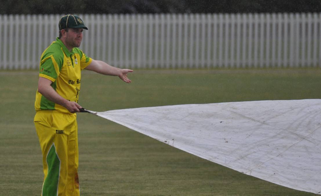 COVERS: Orange CYMS captain Hugh Le Lievre in charge of putting the covers on at Wade Park. Photo: NICK McGRATH